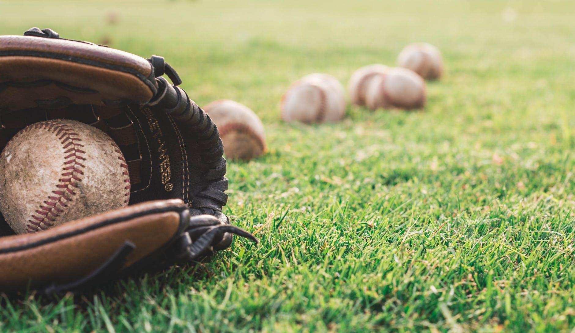 white baseball ball on brown leather baseball mitt